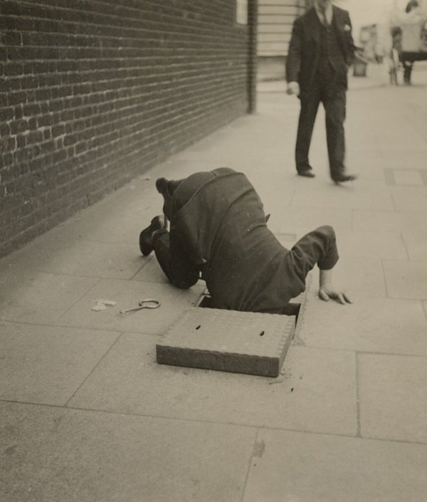 "Dora Maar ""Man looking inside a sidewalk inspection door, London"", c.1935"